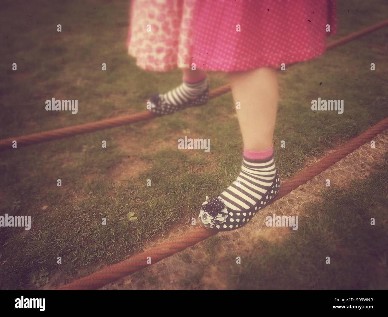 Junges Mädchen Füße auf Drahtseilen balancieren. Stockbild