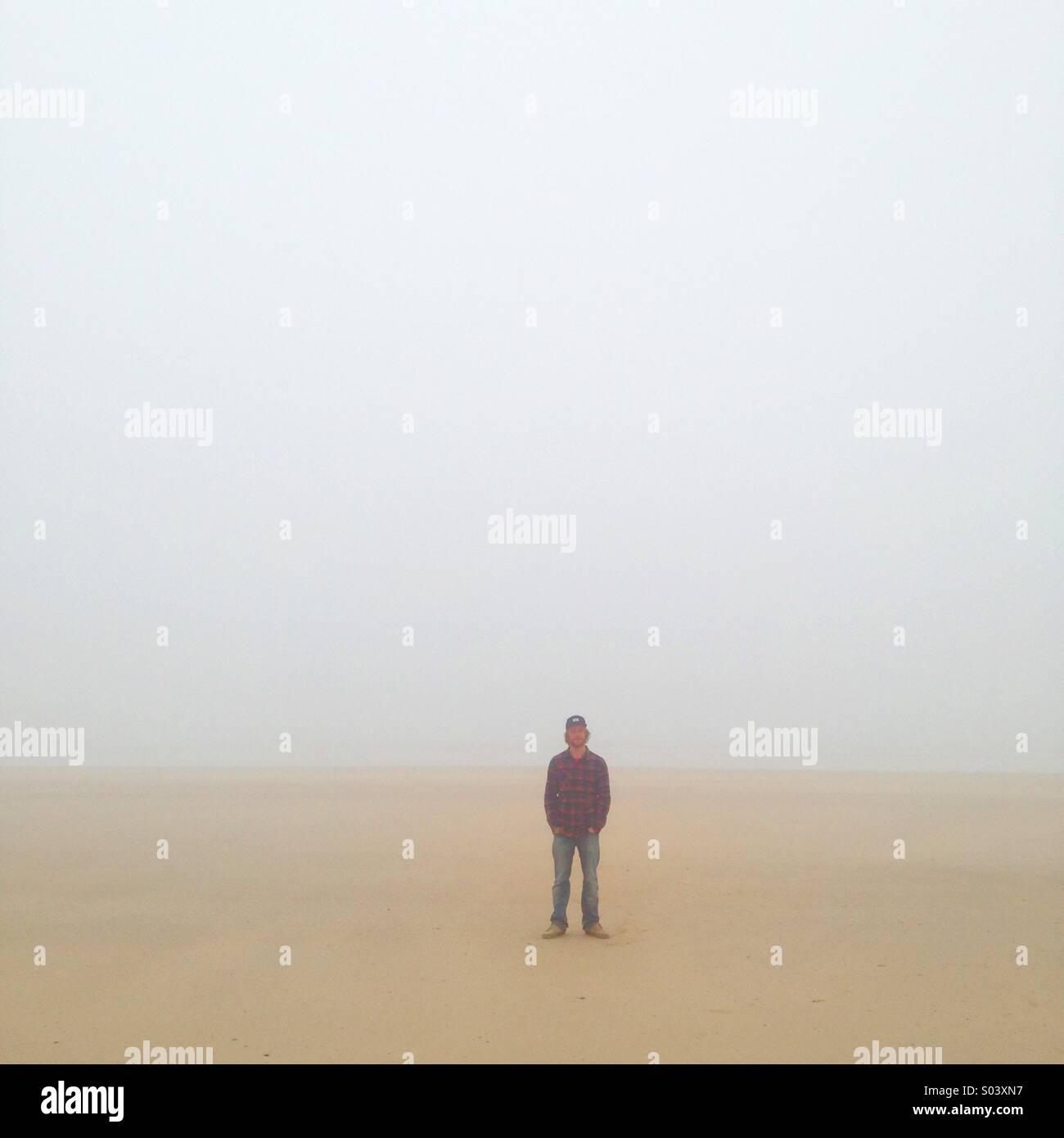 Porträt einer einsamen Person stehen am Strand in schwere See-Nebel. Stockbild