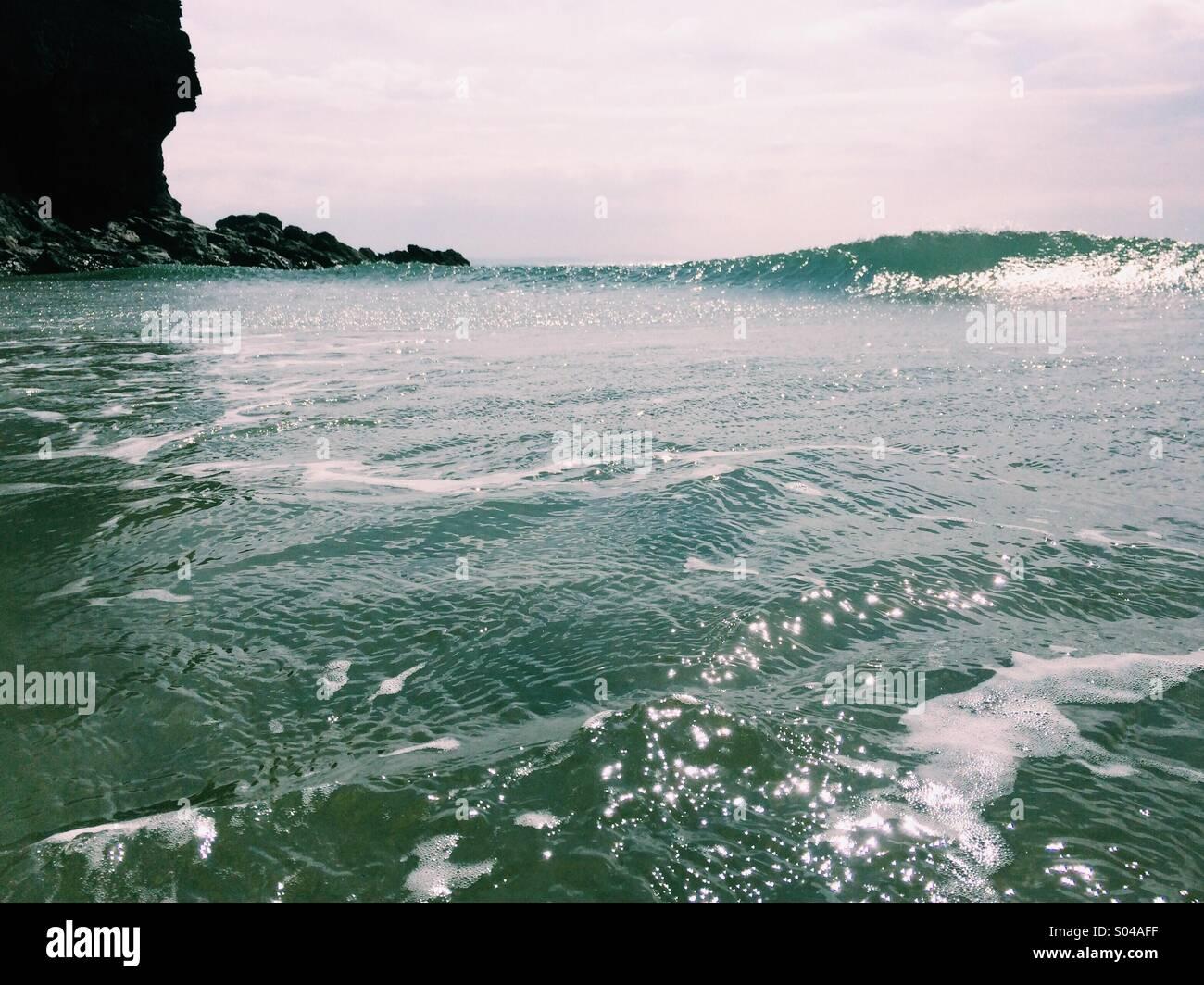 Einer felsigen Landzunge in Cornwall mit einer Welle an einem sonnigen Tag im Meer zu brechen. Stockbild