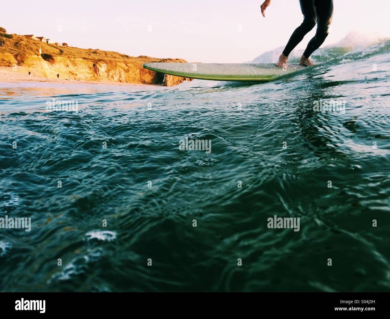 Surfer auf einem Longboard bei Sonnenuntergang im Sommer Stockbild