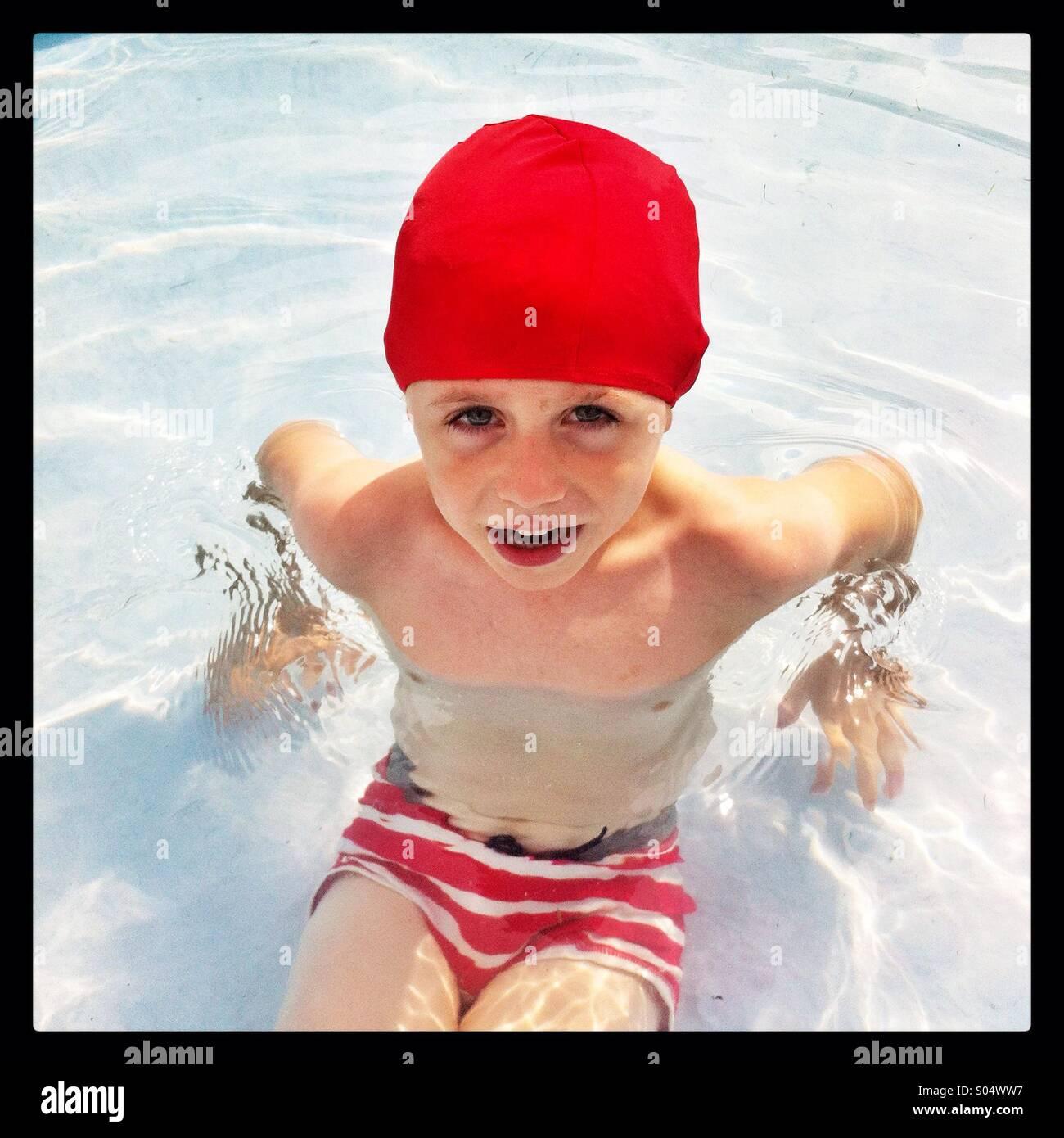 Fünf Jahre alter Junge in einem Schwimmbad eine leuchtend rote Badekappe tragen Stockbild