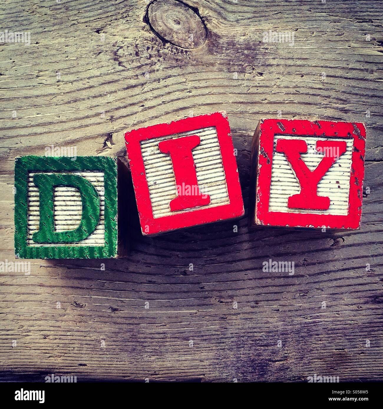 Es ist ein Foto von drei Holz Würfel Spielzeug mit Buchstaben, die das Akronym DIY für Do bilden sie sich Stockbild