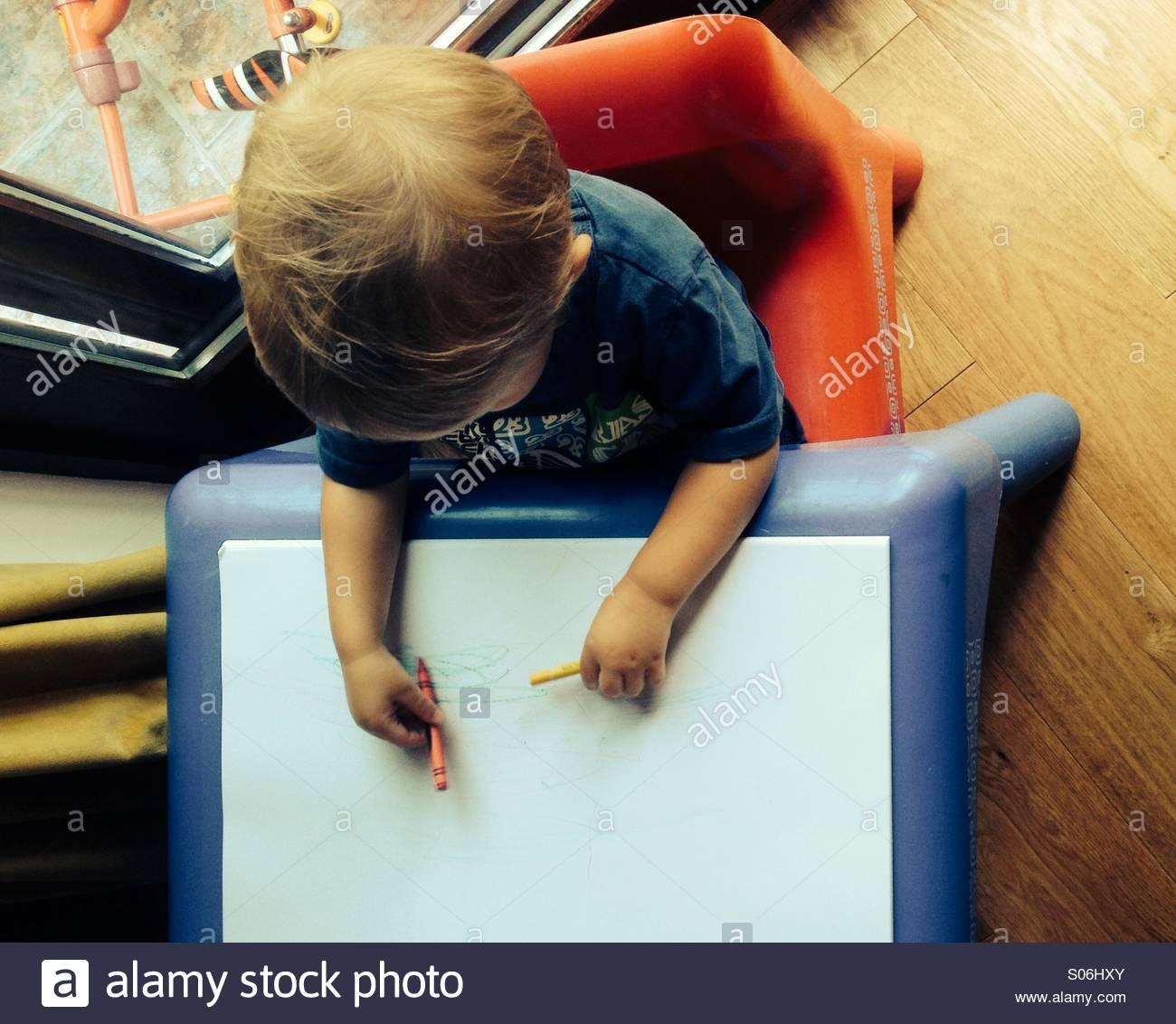 Kleinkind, die ersten Skizzen auf Papier mit Buntstiften zeichnen Stockbild