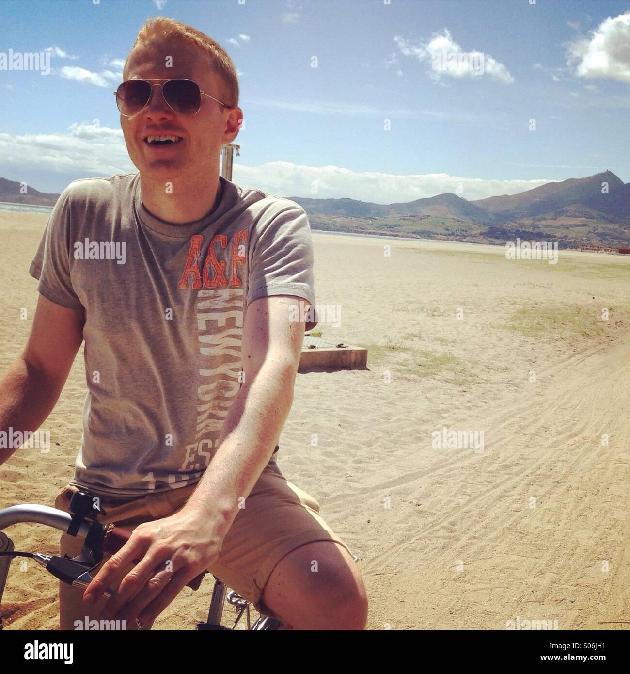 Mann mit Fahrrad am Strand Stockbild