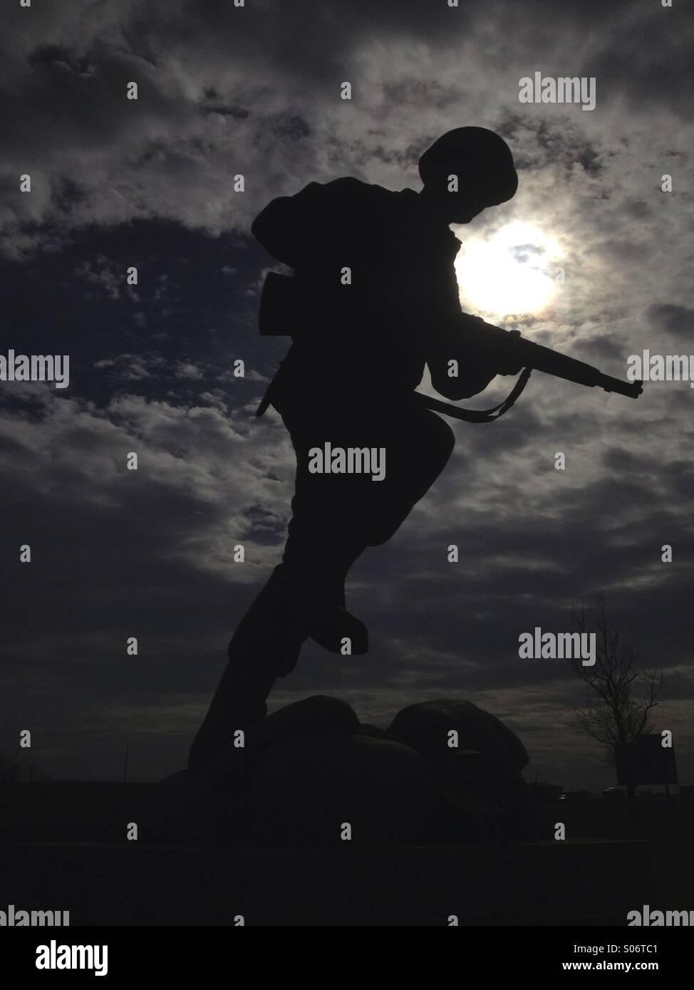 Eine militärische Soldat ist Statue mit scheinbar dramatischen Schwarzarbeit. Stockbild
