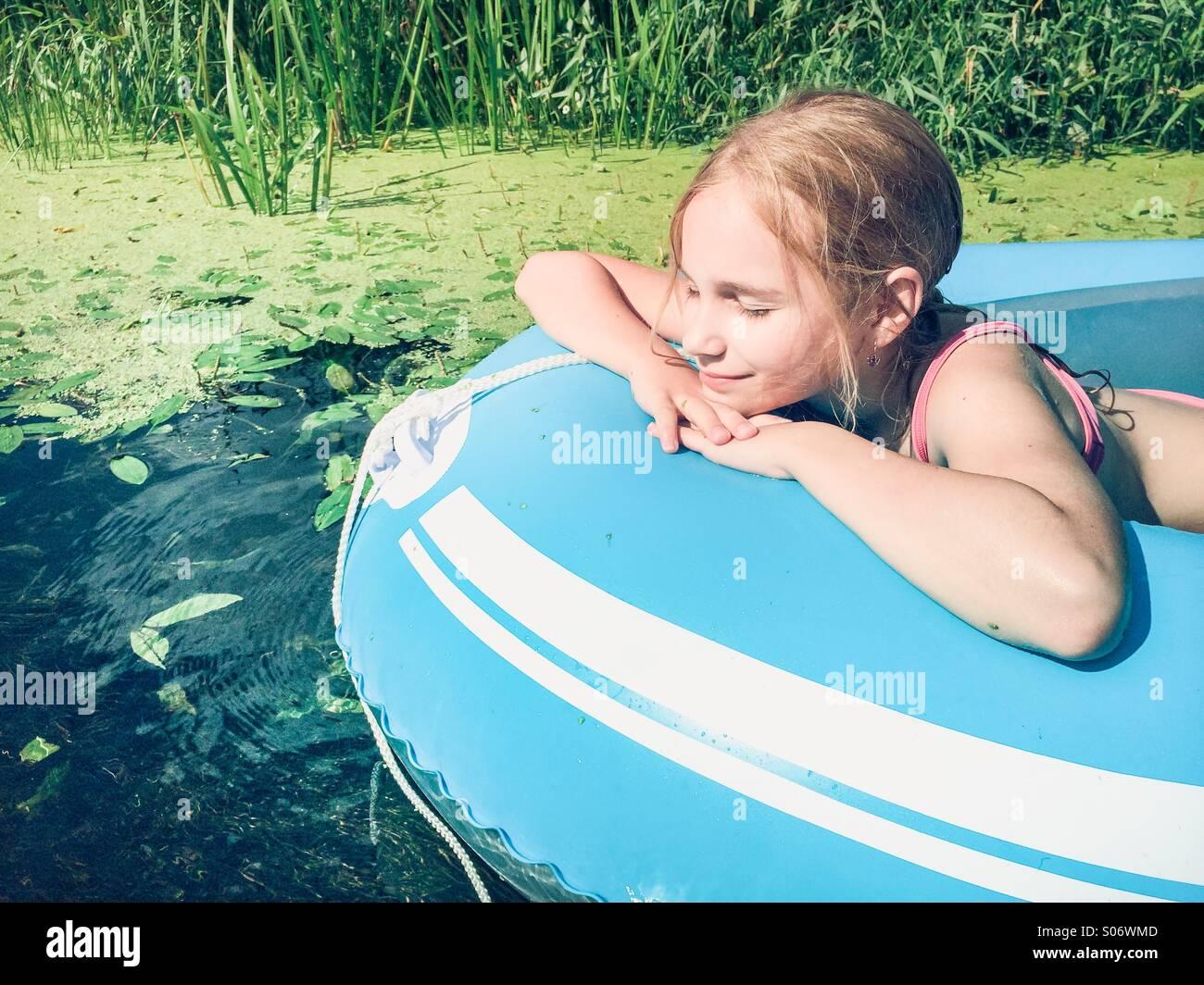Kleines Mädchen sitzt in einem Floß auf einem Fluss mit üppigem Grün Stockbild