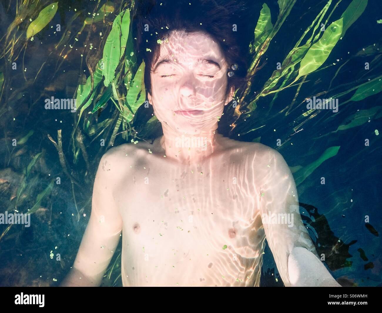 Junge in einem reinen Fluss mit üppigem Grün getaucht Stockbild