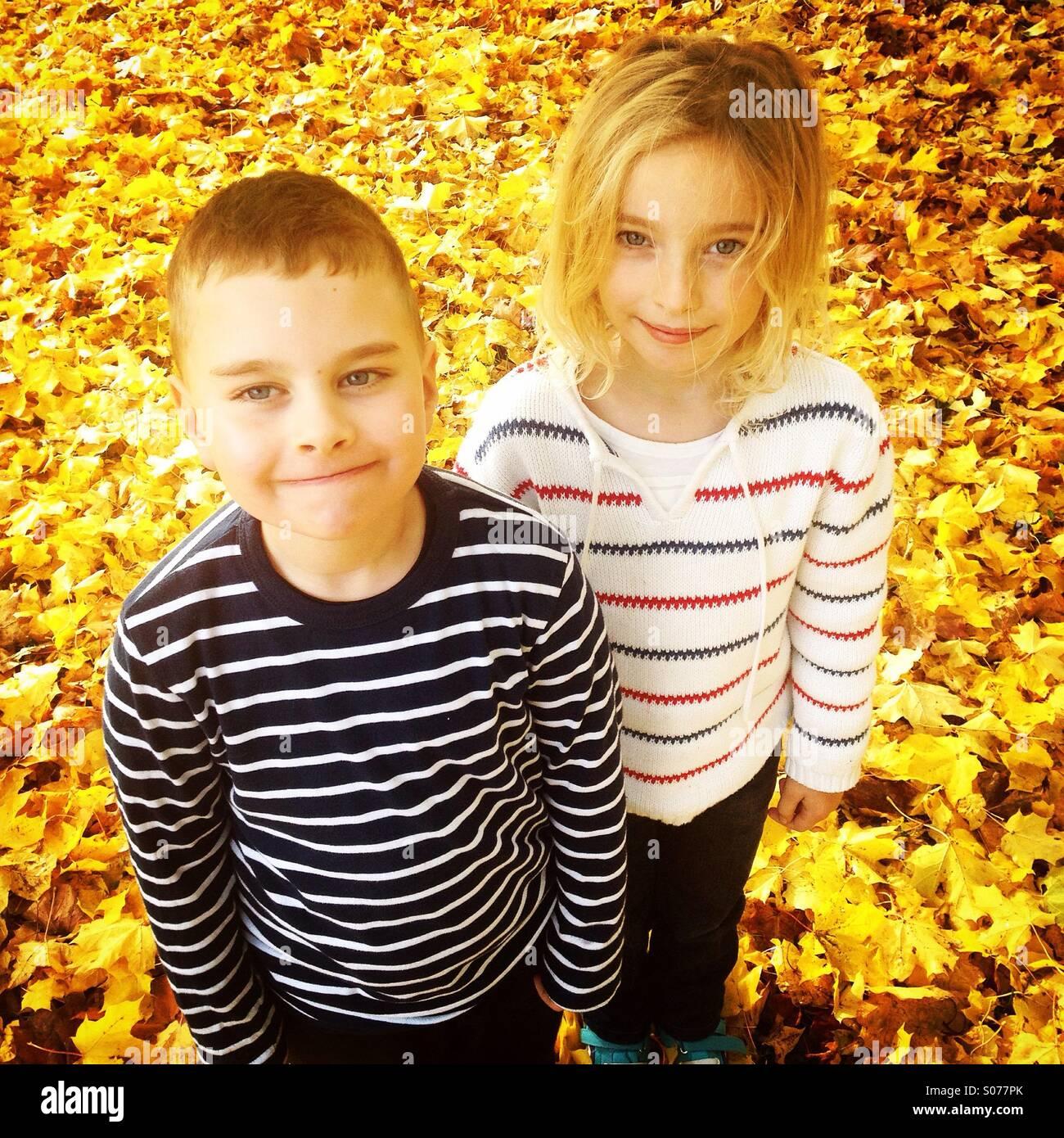 Eine niedliche Bruder und Schwester in einem Feld der goldene gelbe Herbst fallen Blätter Stockbild
