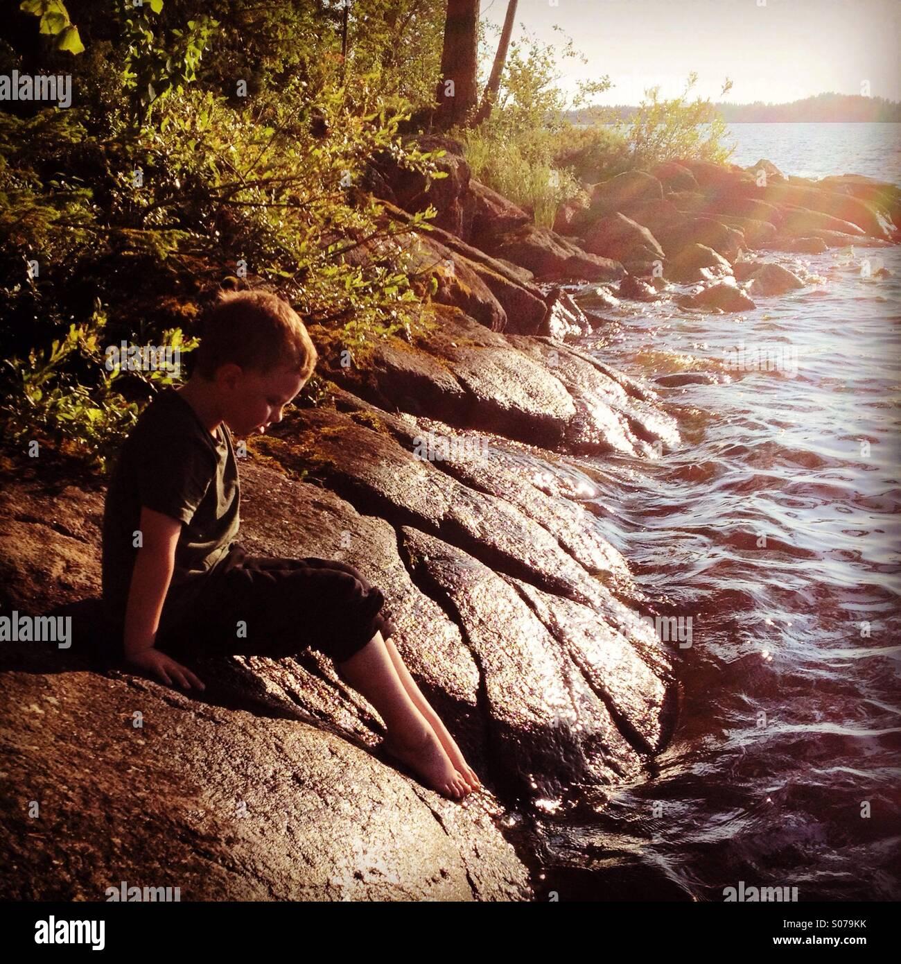 Ein kleiner Junge seine Zehen in das Wasser an einem skandinavischen nordischen Sommerhaus-See Stockbild