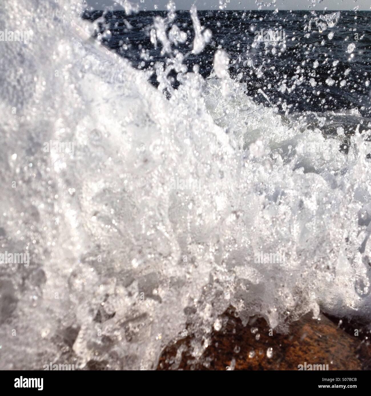 Eine Welle an Felsen gefangen im letzten Moment bevor es das Objektiv trifft brechen Stockbild