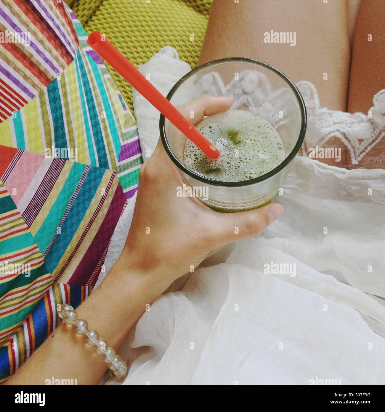 Mädchens Hand Holding Eistee Grüntee auf dem Schoß im weißen Kleid auf hell high-End-Sofa. Stockfoto