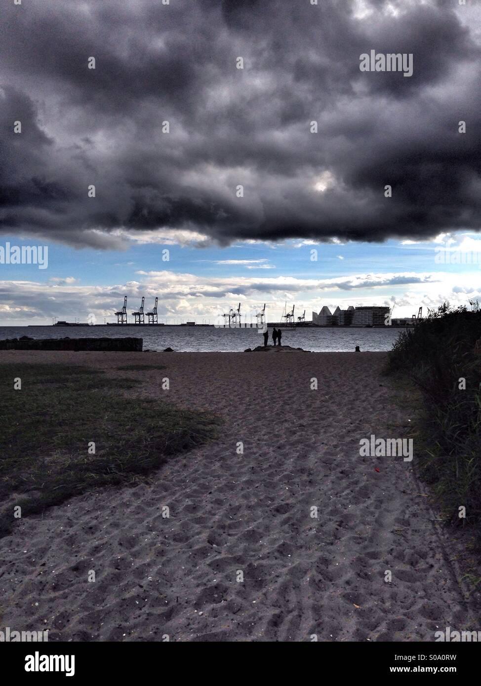 Skandinavischen Landschaft, Sturm am Strand, mit riesigen und dunkle Wolken, einen hellen und blauen Himmel im Hintergrund, Stockbild