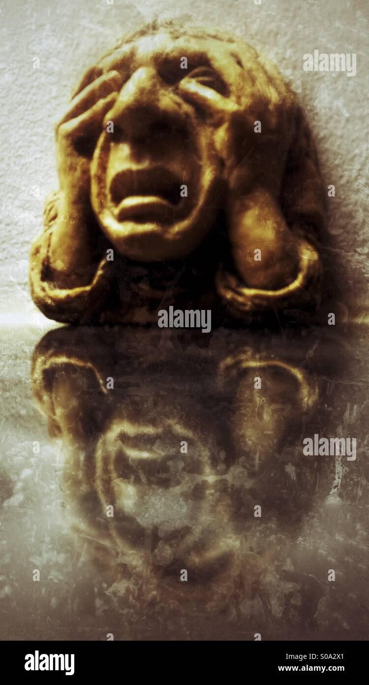 """Stein gemeißelt Kopf genannt """"Elend"""" Wasserspeier (AKA groteske) Wand-Plakette an der Universität Stockbild"""