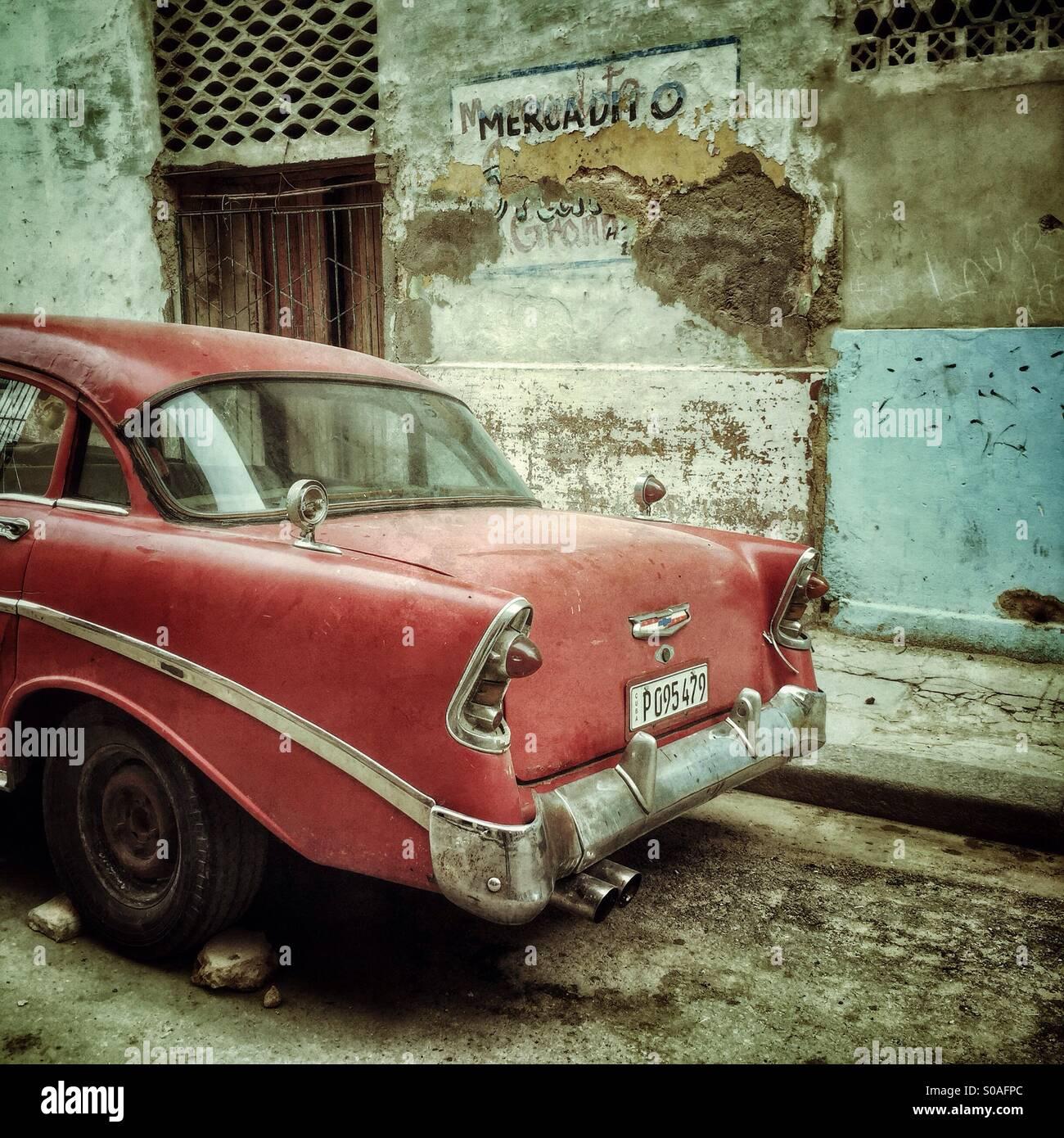 Rückansicht eines roten Jahrgang kubanische Auto, mit einem Peeling lackiert verfallende Außenwand geparkt. Stockbild