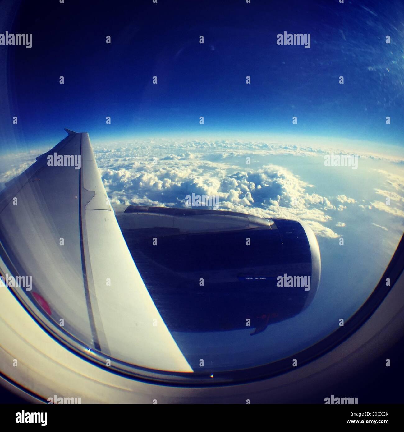 Blick auf den Flügel eines Flugzeugs an die Krümmung der Erde Stockbild