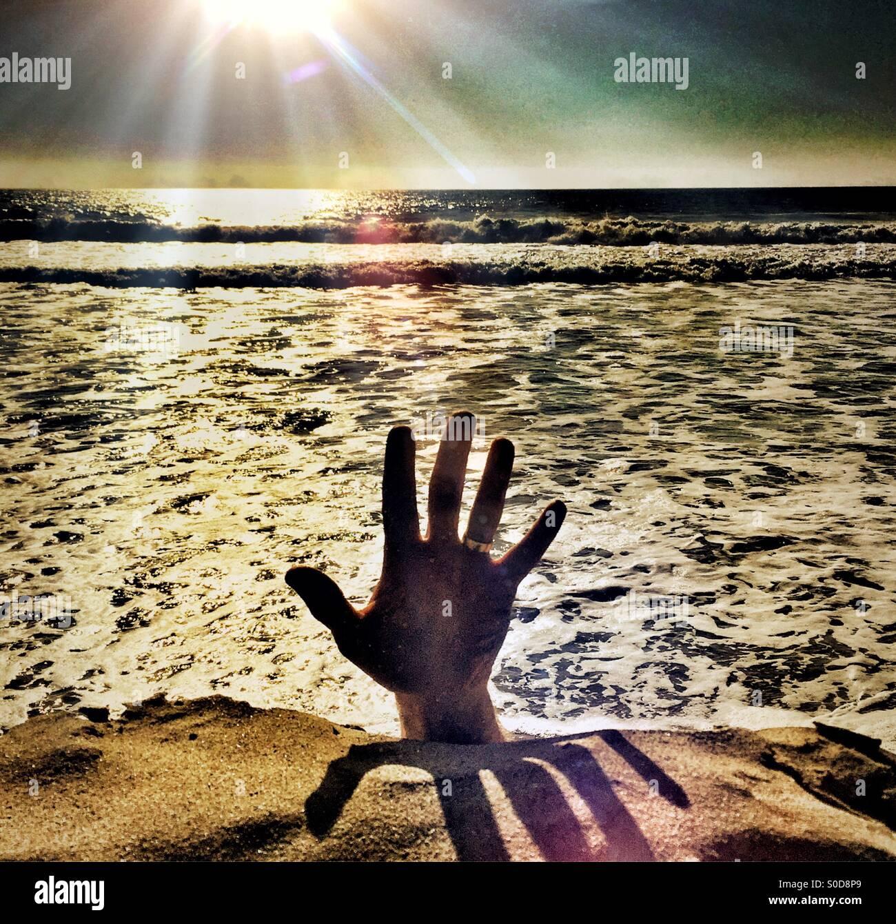 Hilfe! Hand greift von oben aus dem Wasser ins Licht Stockbild