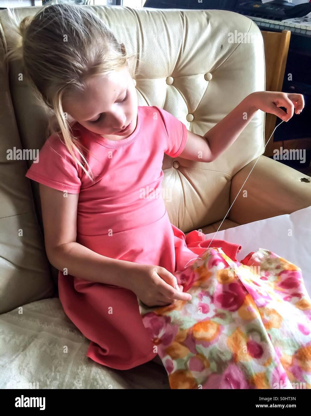 Mädchen näht einen Kissenbezug von hand Stockbild