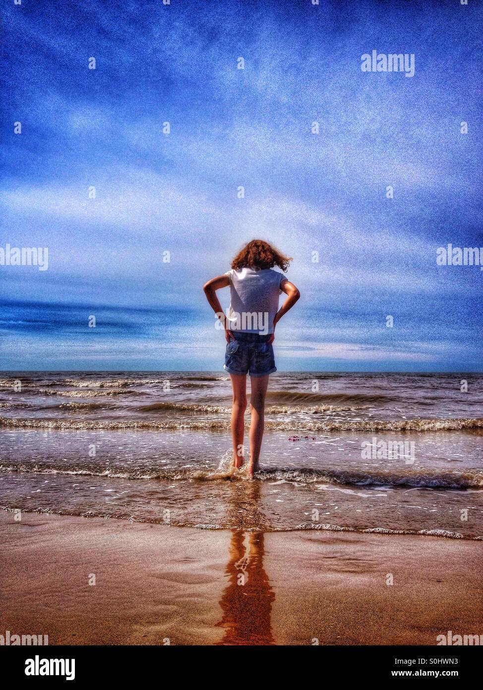 Junges Mädchen im Meer paddeln Stockbild