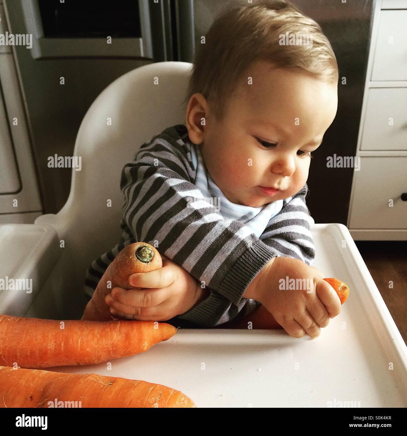 Baby Junge sitzt in seinem weißen Hochstuhl mit gekreuzt, Hände halten, zwei frische nicht geschälte Stockbild