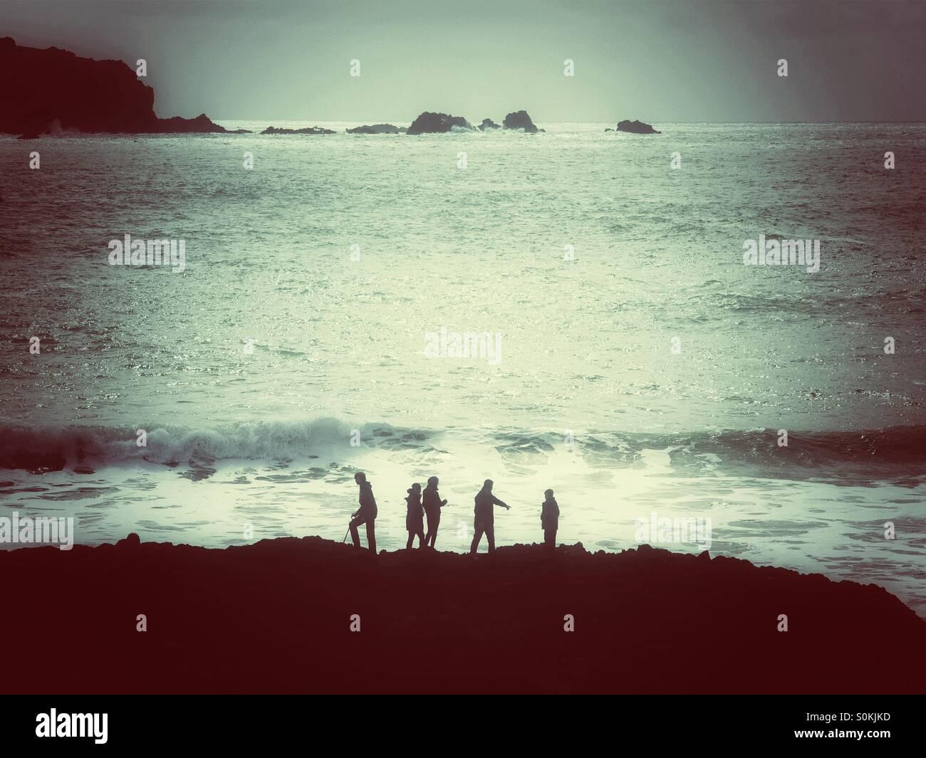 Fünf Personen gegen einen Ozean mit rollenden Wellen. Stockbild