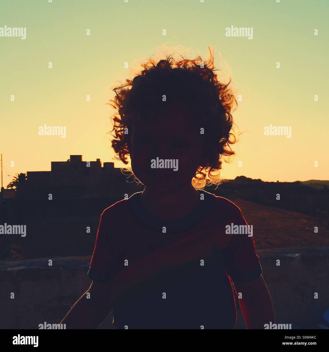Leuchtende Silhouette eines jungen mit Sonnenuntergang im Hintergrund Stockbild