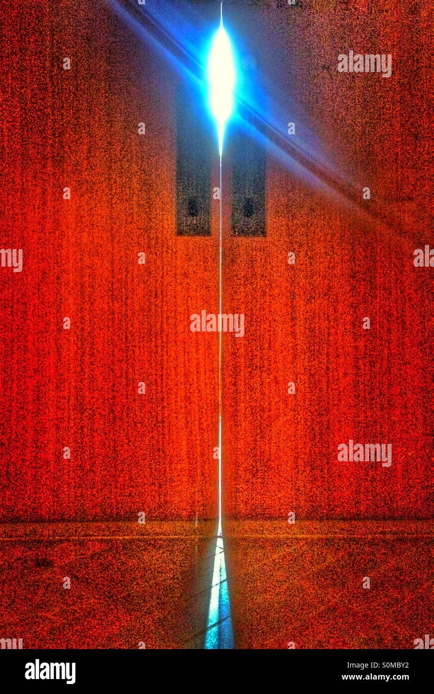 Rote Tür mit Licht spähen durch Stockbild
