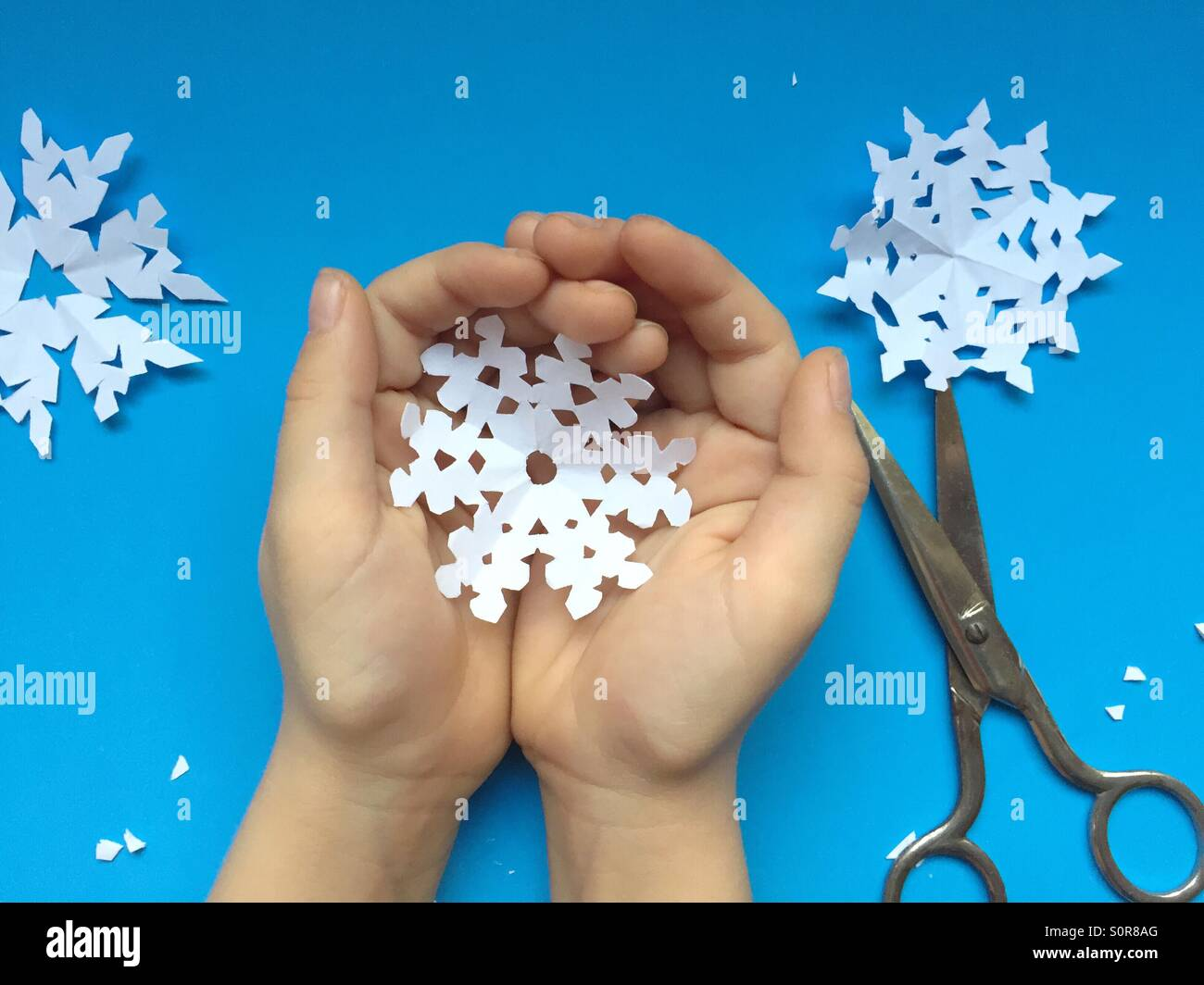 Kind hält Papier-Schneeflocke Stockbild