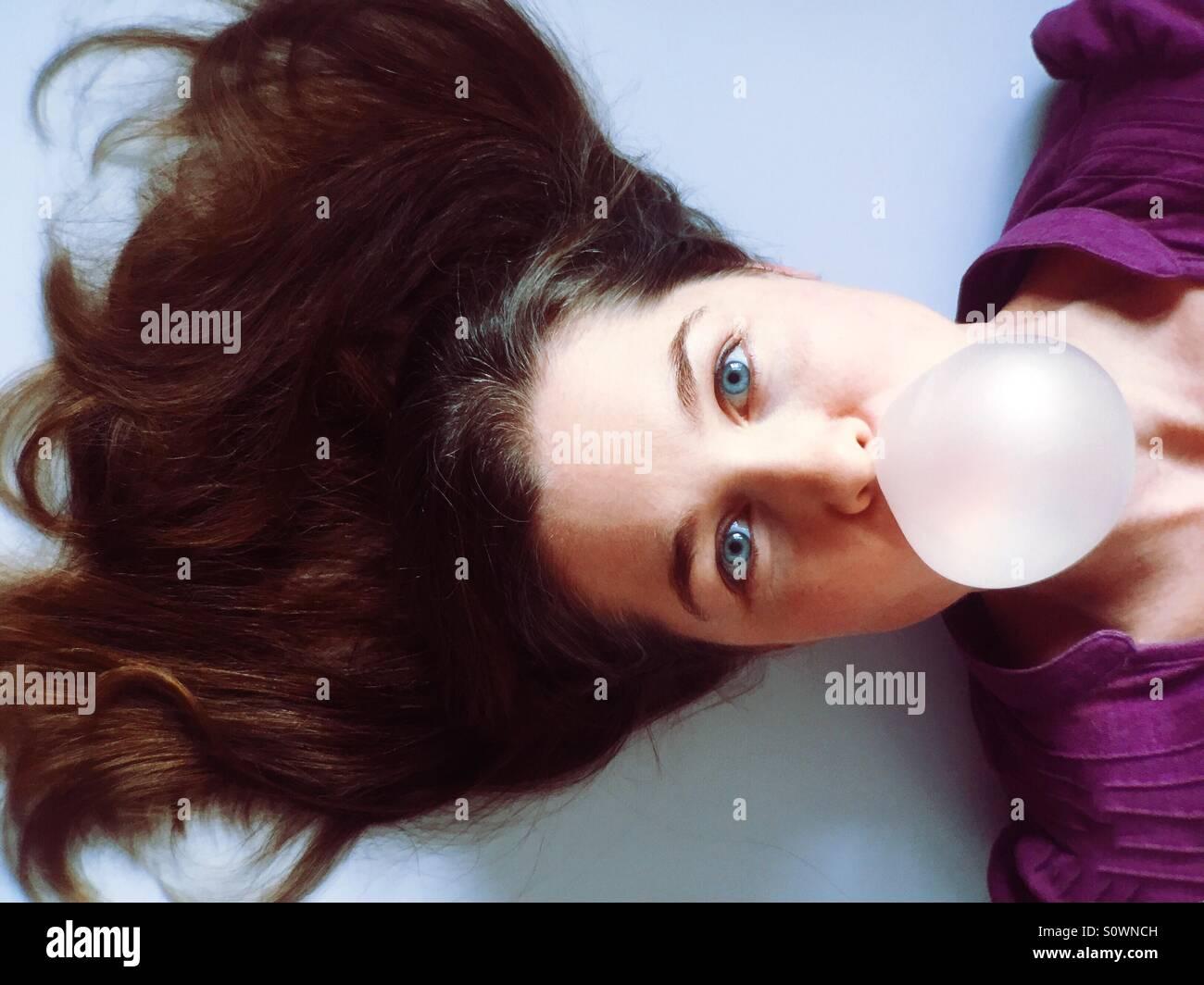 Frau bläst eine Kaugummi-Blase Stockfoto
