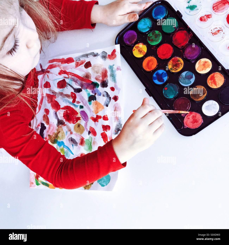 Bild eines jungen Mädchens mit Wasserfarben um Entwürfe auf Papier zu machen. Stockbild