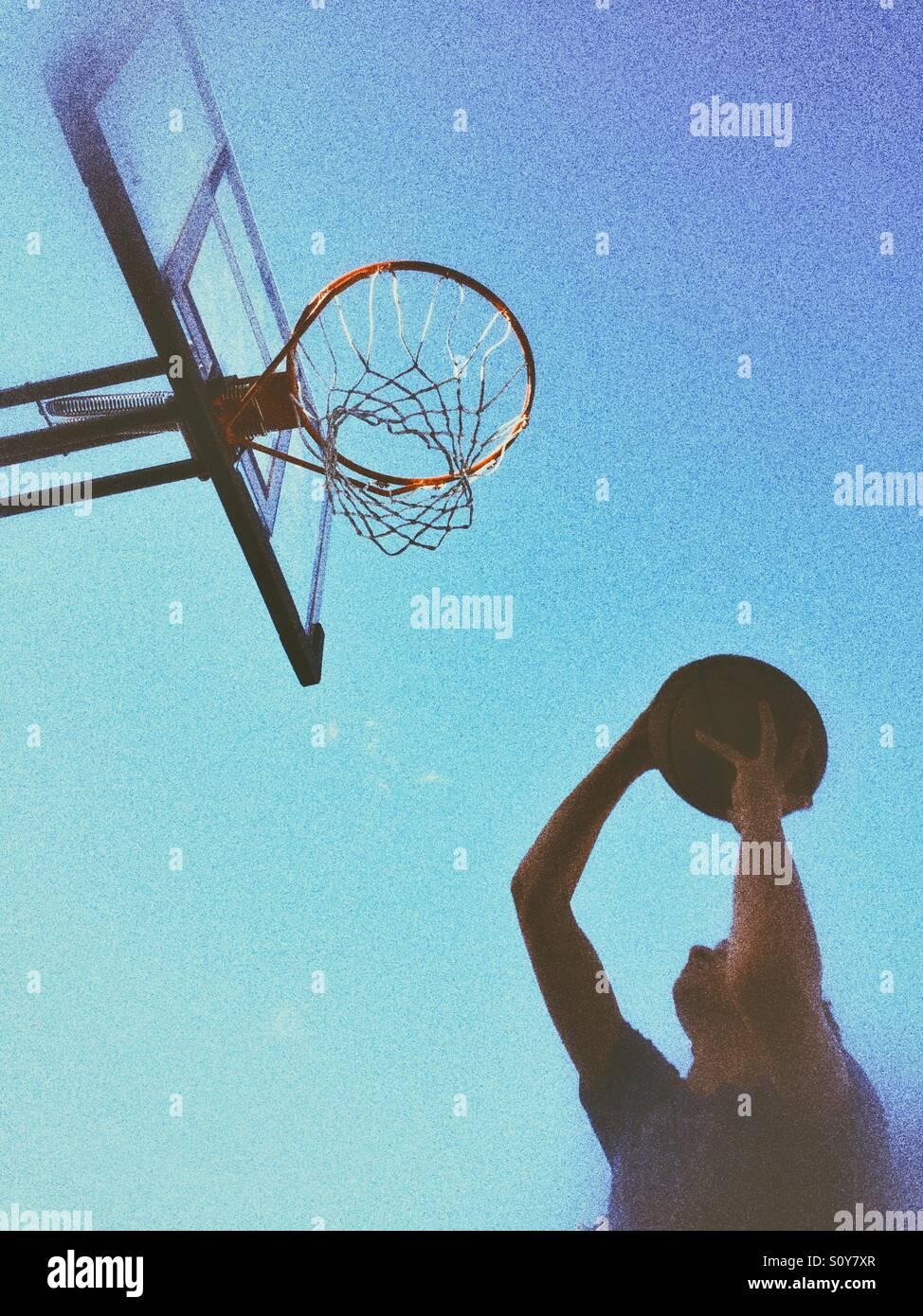 Teenager-Jungen schießen einen Basketball. Im Freien Schuss, natürliches Licht, körnige bearbeiten. Stockbild