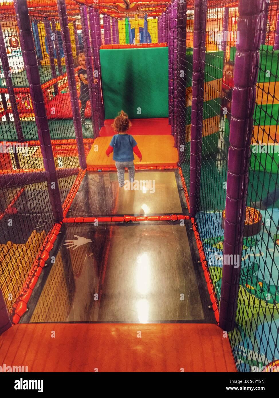 Kleinkind spielt in indoor-Spielplatz m Stockbild
