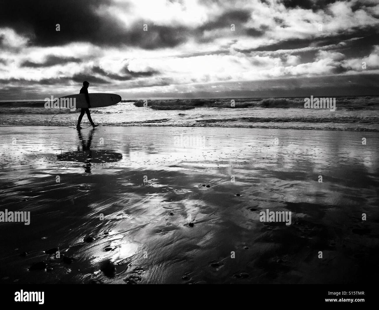 Eine Surfer trägt seinem Brett, als er entlang Süßwasser Weststrand in Süd-Wales Oktober 2016 Stockbild