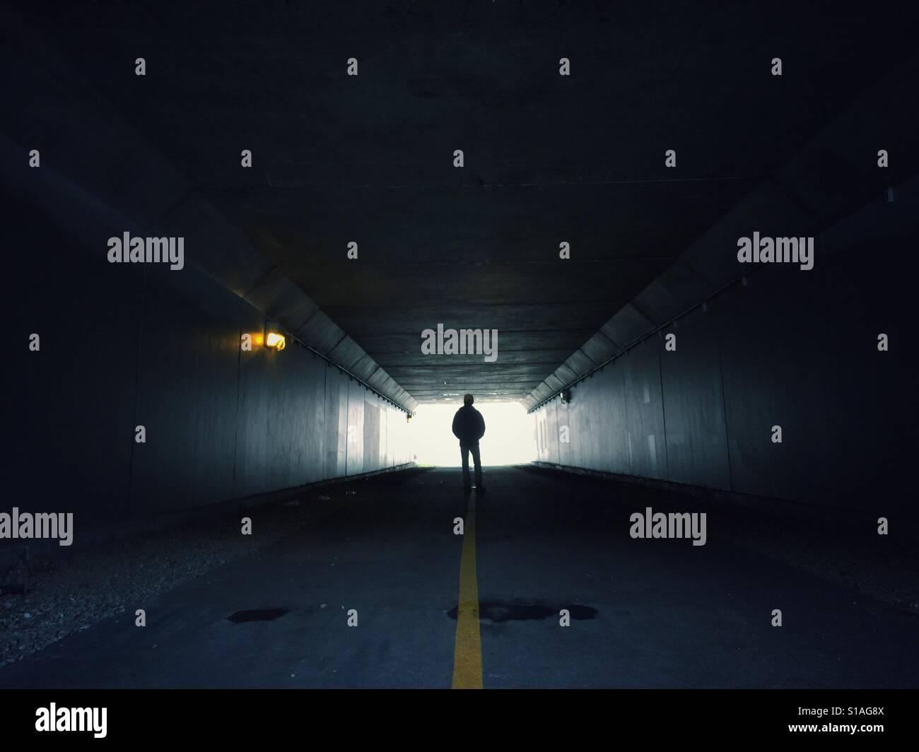 Mann steht am Ende eines dunklen Tunnels Stockfoto