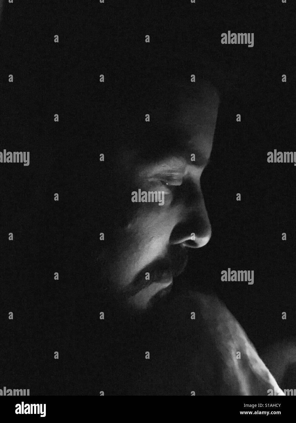 Mann in Dunkelheit mit Licht auf Gesicht. Stockfoto