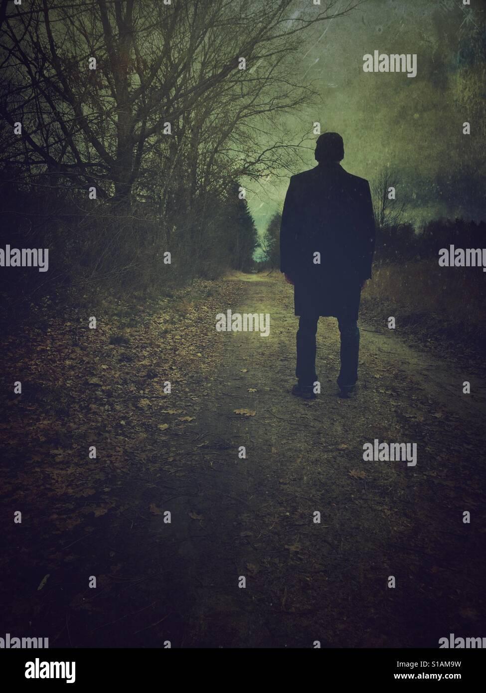 Rückansicht eines Mannes mit einem Mantel stehen auf einer Land-Straße Stockfoto