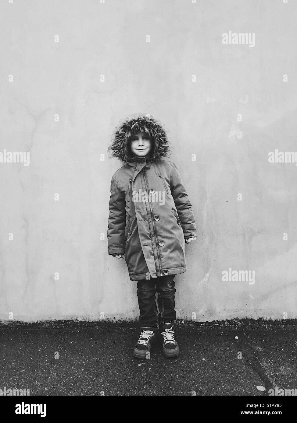 Young Boy entlang der Wand Stockfoto