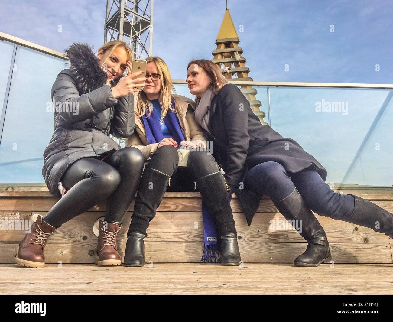 3 Mädchen spielen mit iphone Stockfoto