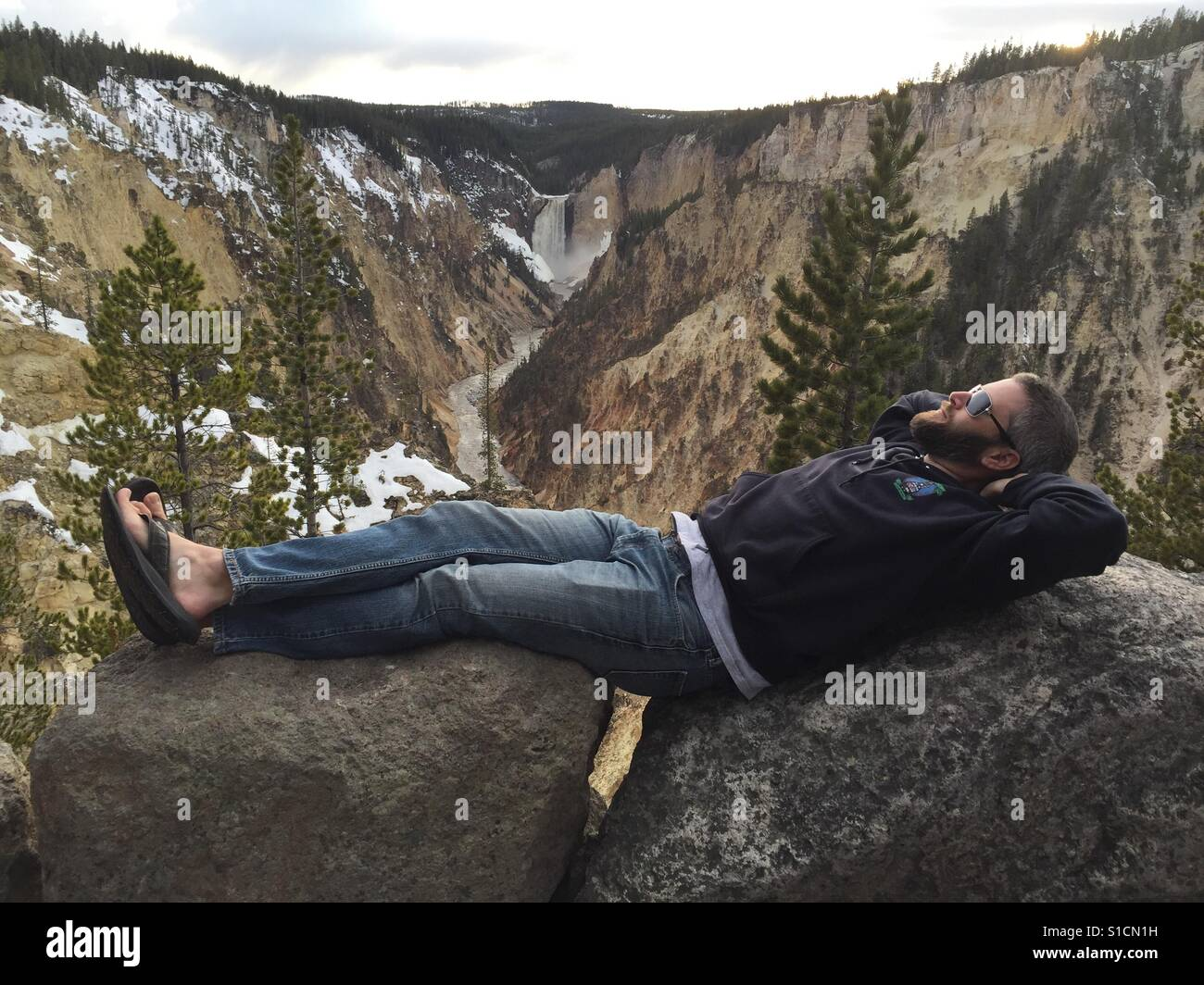 Ein Mann zurücklegt über Felsblöcke mit Upper Falls im Yellowstone National Park im Hintergrund. Stockfoto