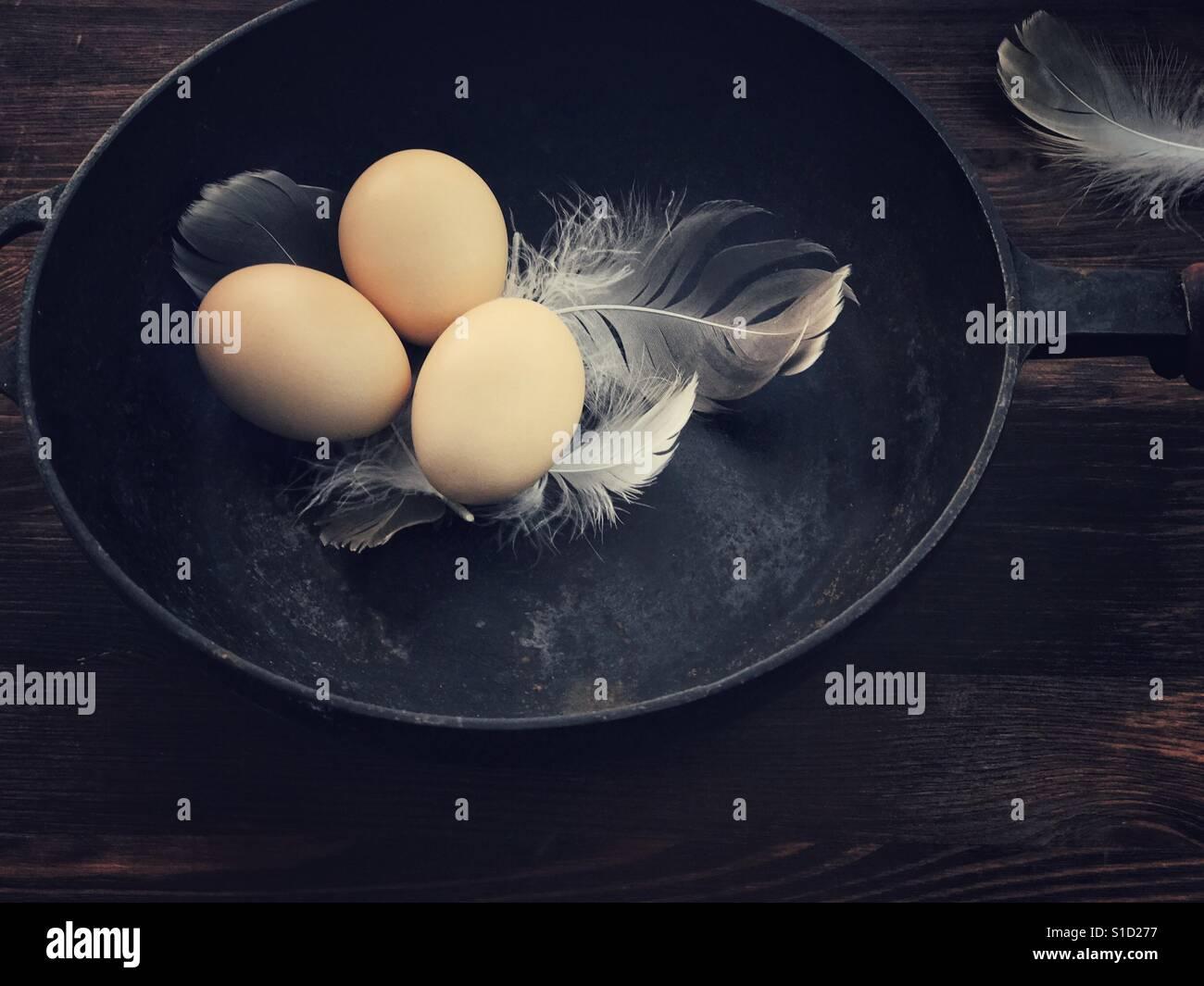 Drei Hühnereier in einer schwarzen gusseisernen Pfanne Stockfoto