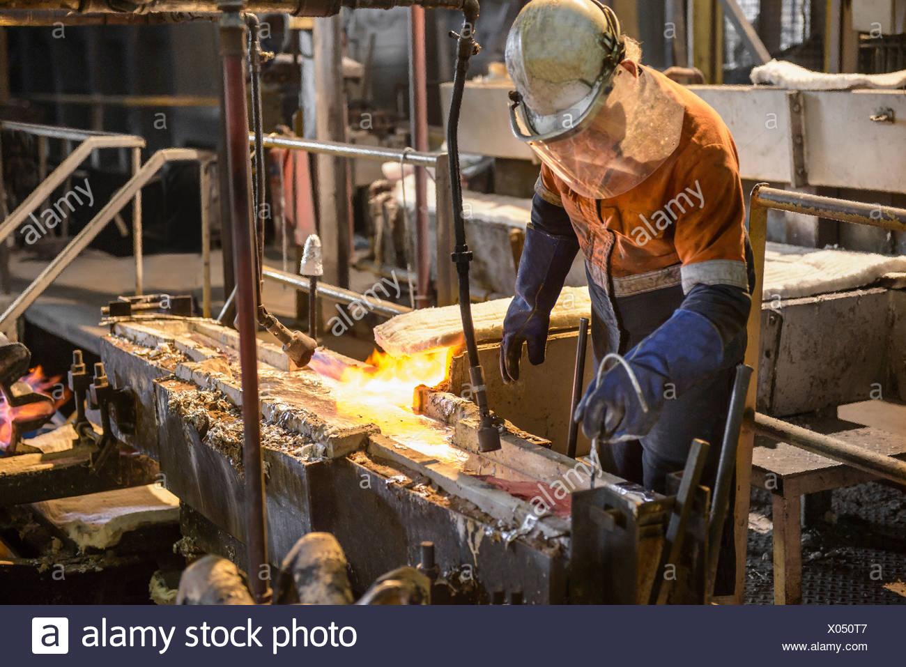 Arbeiter, die Schmelze an Aluminium-recycling-Anlage testen Stockbild