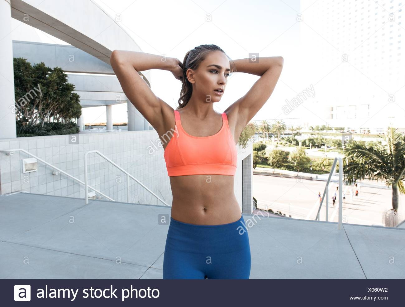 Junge Frau trägt Sport-BH, Hände hinter dem Kopf, wegschauen Stockbild