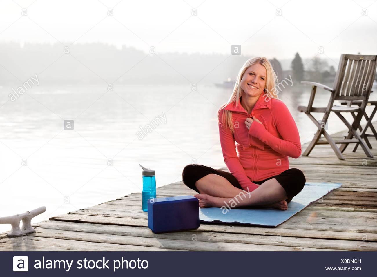 Eine junge Frau hanging out an einem Dock über Lake Washington und lächelnd in die Kamera während der Sitzung auf eine Yoga-Matte. Stockbild