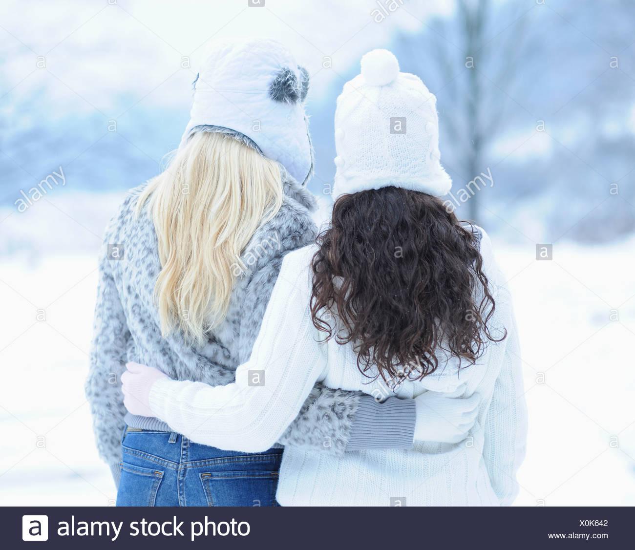 Ansicht von hinten von zwei jungen Frauen umarmen Wintertag Stockbild