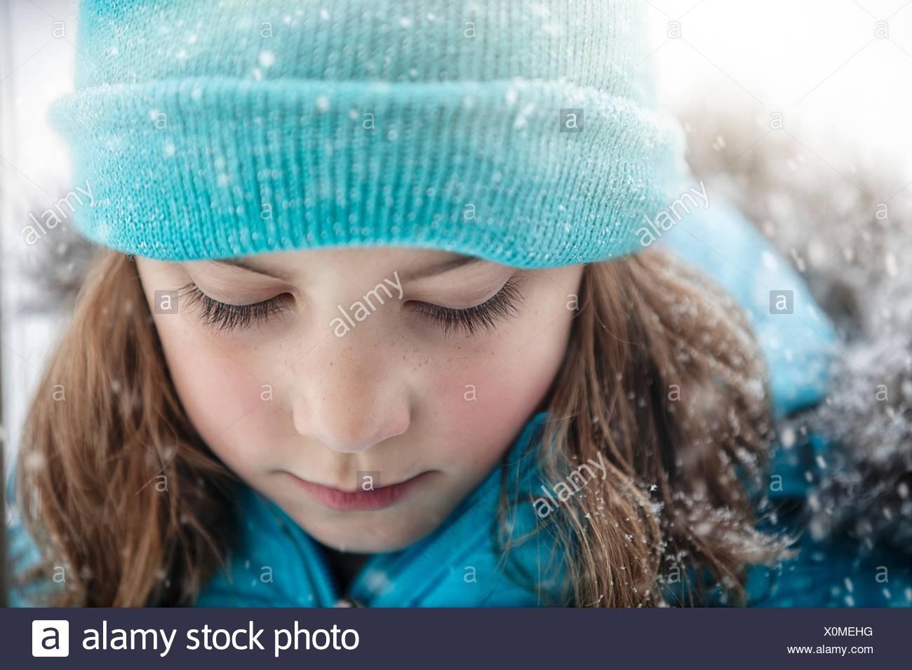 Porträt eines Mädchens tragen stricken Hut blickte, schneit hautnah Stockbild