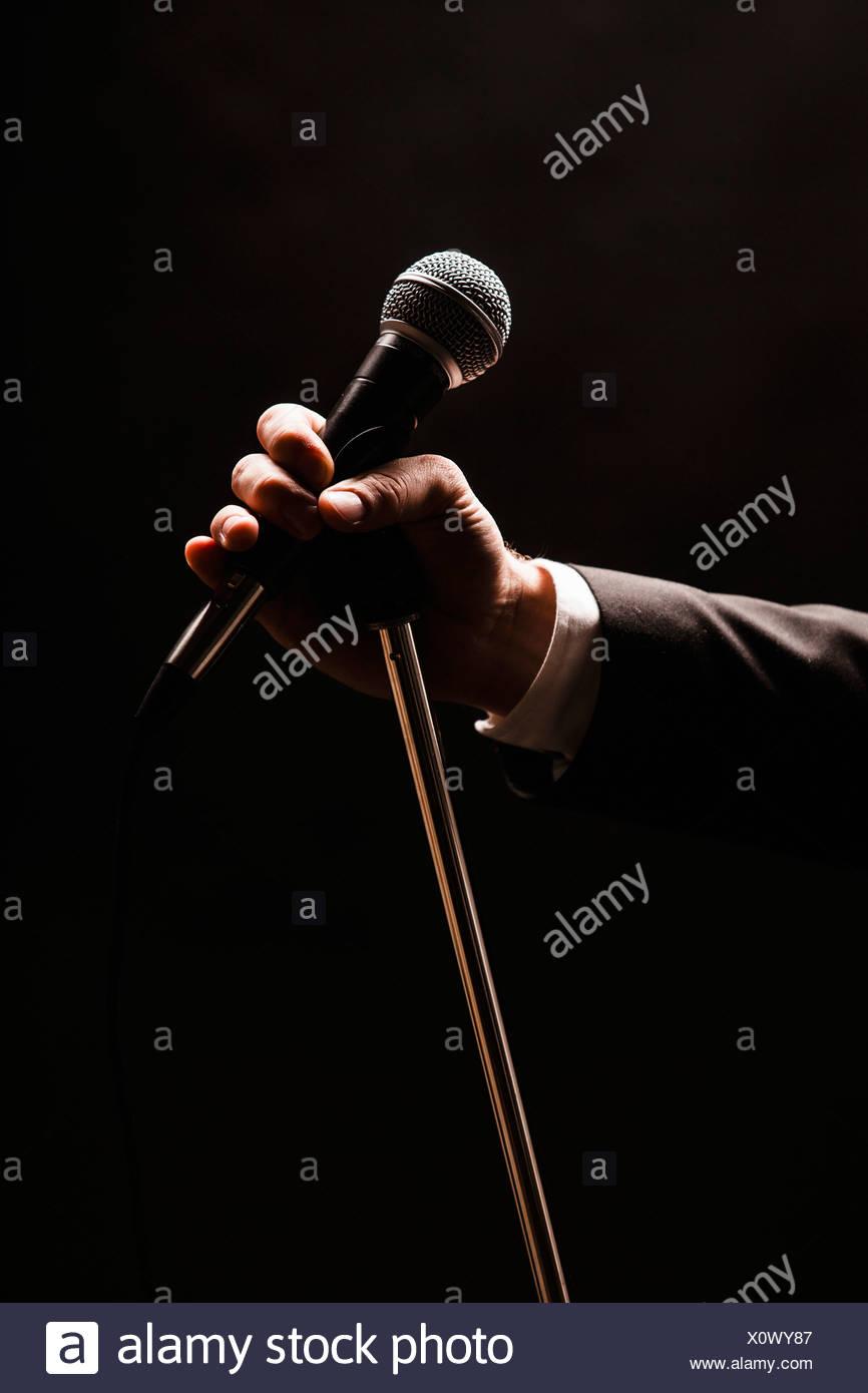 Hand mit Mikrofon auf schwarzem Hintergrund Stockbild