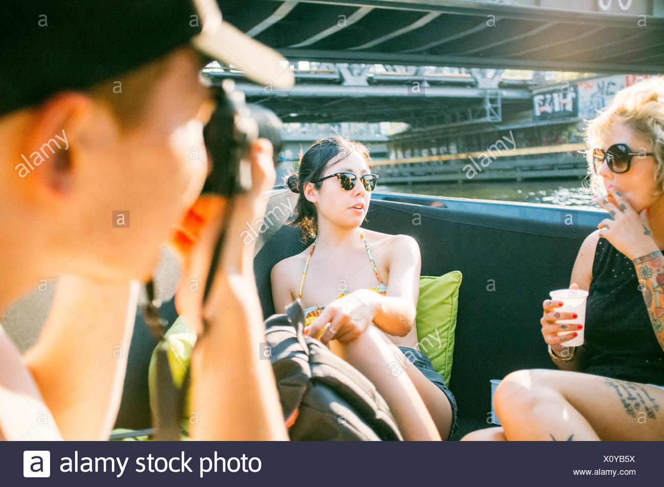 Mann fotografiert Frauen beim stillstehen auf Boot Stockbild