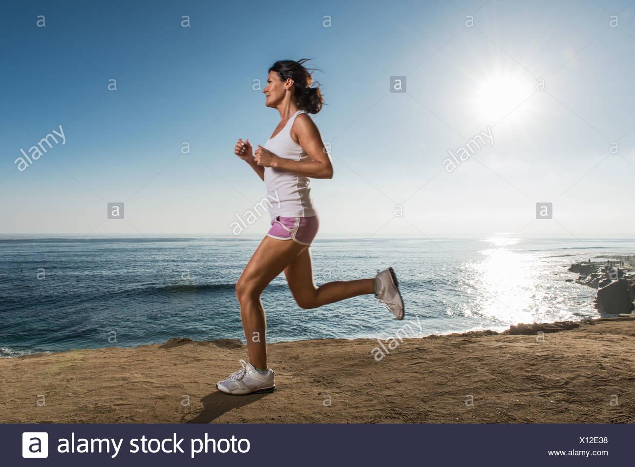 Mitte Erwachsene Frau Joggen entlang der Klippe Stockbild