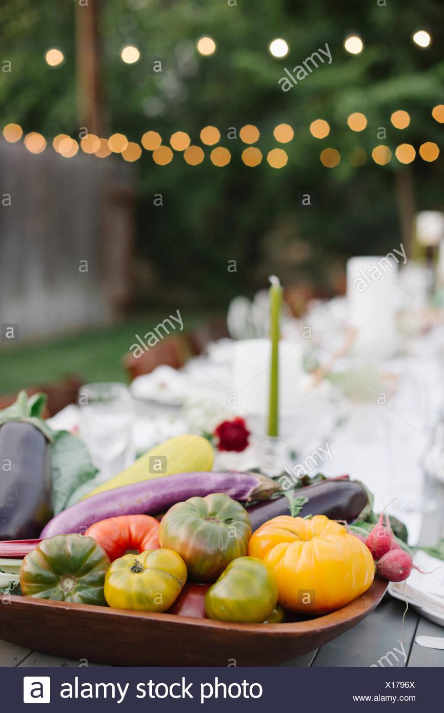 Langer Tisch set mit Teller und Gläser, Essen und trinken in einen Garten, eine Schüssel mit Gemüse im Vordergrund. Stockbild