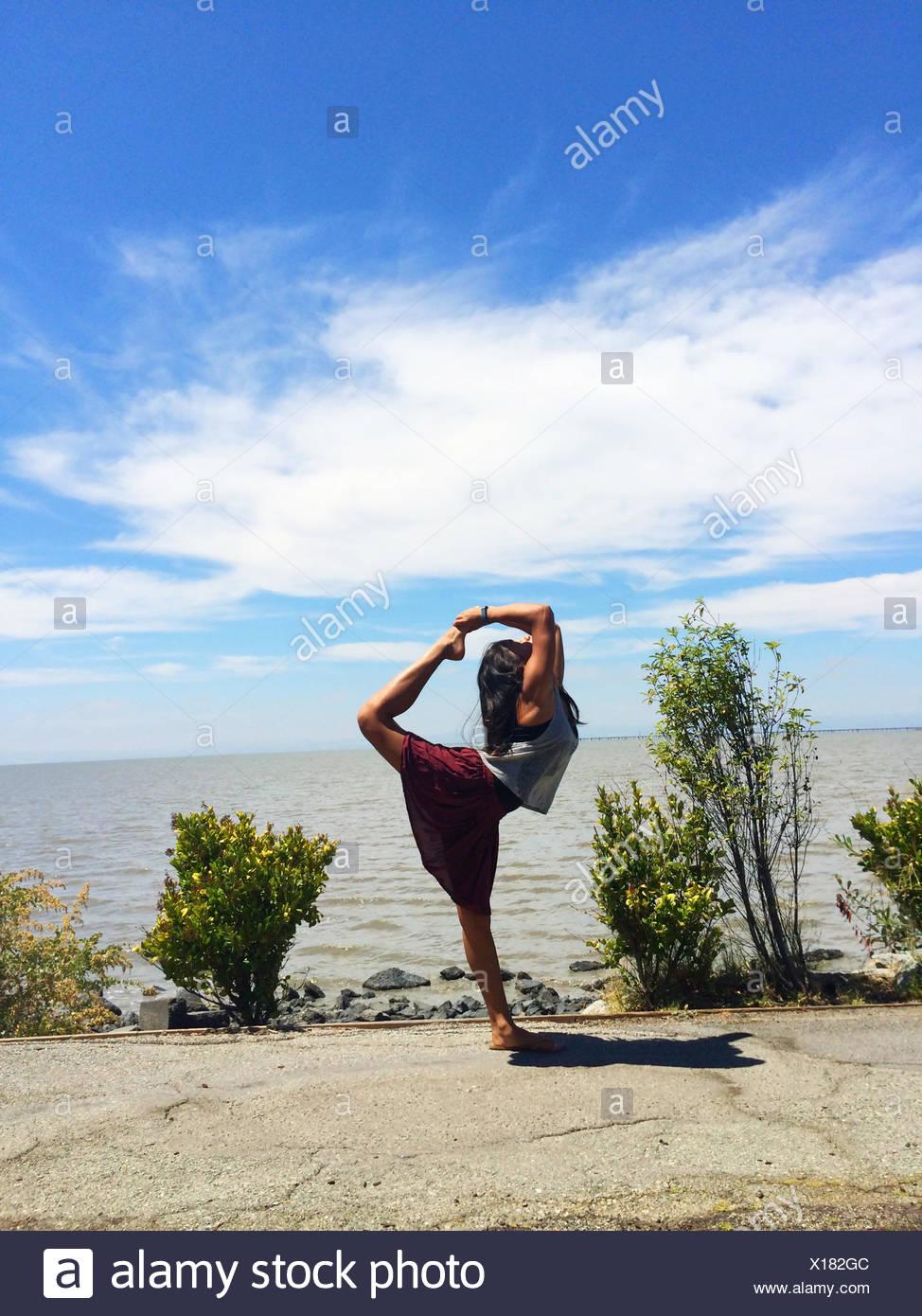 Mädchen tun stehenden Bogen ziehen Yoga-Pose am Strand Stockbild