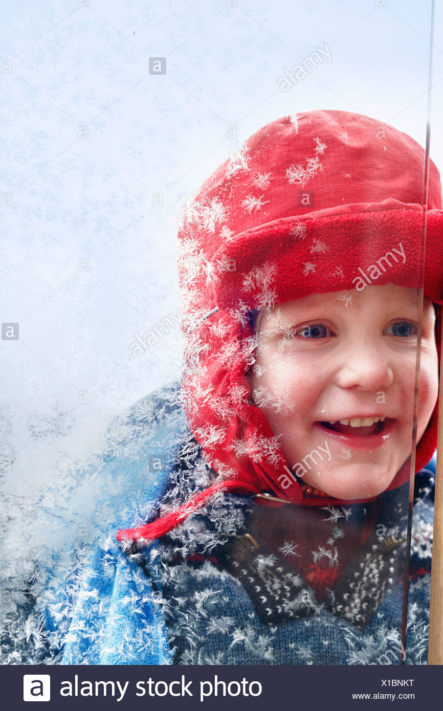 Lächelnden jungen suchen in frostigen Fenster Stockbild